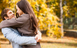 Smiling couple hugging over autumn background. Love, relationship, family, season and people concept - smiling couple hugging over autumn natural background Royalty Free Stock Images
