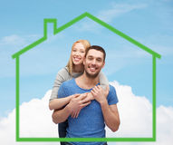Smiling couple hugging over green house Royalty Free Stock Image