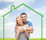 Smiling couple hugging over green house Royalty Free Stock Photo
