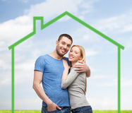 Smiling couple hugging over green house Stock Image