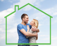 Smiling couple hugging over green house Royalty Free Stock Images