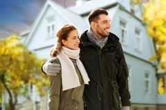 Smiling couple hugging over house in autumn stock photography
