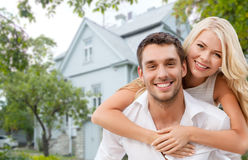 Smiling couple hugging over house background. Love, people, real estate, home and family concept - smiling couple hugging over house background Royalty Free Stock Photos
