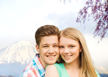 Smiling couple hugging over mountains background Stock Images