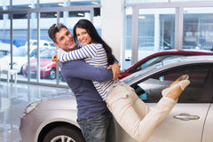Smiling couple hugging and smiling at camera. At new car showroom royalty free stock images