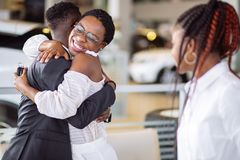Couple collecting new car from salesman on lot. Smiling couple hugging and smiling at camera at new car showroom stock image