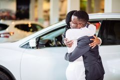 Couple collecting new car from salesman on lot. Smiling couple hugging and smiling at camera at new car showroom royalty free stock photos