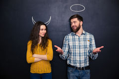 Smiling couple imitating devil and angel over chalkboard background Royalty Free Stock Photography