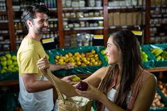 Smiling couple interacting with each other in organic section Royalty Free Stock Images