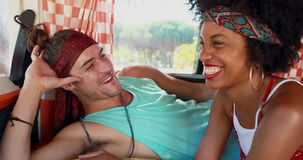 Couple interacting with each other while relaxing in camper van 4k. Smiling couple interacting with each other while relaxing in camper van 4k stock footage