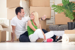 Smiling couple with key of new home. Smiling couple sitting on floor with key of new home stock image