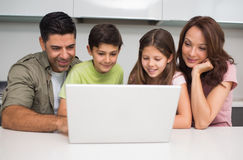 Smiling couple with kids using laptop Stock Photos