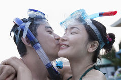 Smiling couple kissing on the cheek wearing snorkeling gear in the pool Stock Image