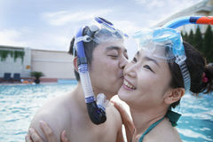 Smiling couple kissing on the cheek wearing snorkeling gear in the pool Stock Photography