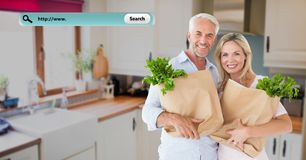 Smiling couple in kitchen holding grocery bags Stock Images