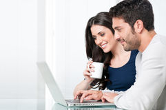 Smiling couple with laptop. Happy modern couple surfing the net and working on laptop at home royalty free stock image
