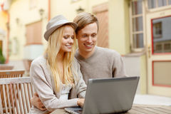 Smiling couple with laptop computer in cafe Royalty Free Stock Photography