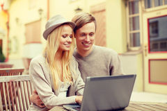 Smiling couple with laptop computer in cafe Royalty Free Stock Image