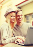 Smiling couple with laptop computer in cafe Stock Images