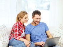 Smiling couple with laptop computer at home Stock Photos