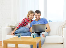 Smiling couple with laptop computer at home. Home, technology and relationships concept - smiling couple with laptop computer at home royalty free stock photos