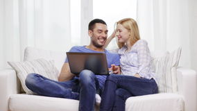 Smiling couple with laptop computer at home stock footage