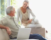 Smiling couple with laptop on couch at home Stock Images