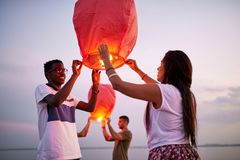 Smiling couple launching Chinese lanterns as symbol of love royalty free stock images