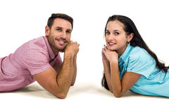 Smiling couple laying on the floor face to face looking at the camera Stock Image