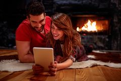 Smiling couple laying on floor and using tablet at home. Front of fireplace stock images