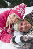 Smiling couple laying together in snow Royalty Free Stock Photos