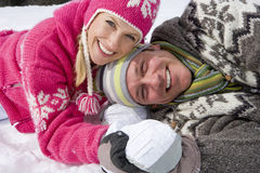 Smiling couple laying together in snow Royalty Free Stock Photography