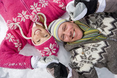 Smiling couple laying together in snow Royalty Free Stock Image