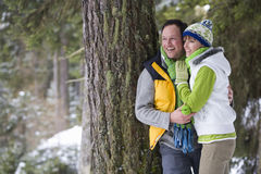 Smiling couple leaning against tree trunk in woods Stock Images