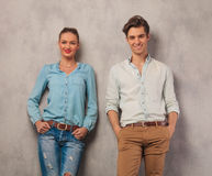 Smiling couple leaning against the wall with hands in pockets Stock Photos