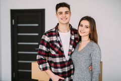 Smiling couple leaning on boxes in new home. Young couple moving to a new apartment together relocation. Smiling couple leaning on boxes in new home stock photography