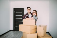 Smiling couple leaning on boxes in new home. Young couple moving to a new apartment together relocation Stock Image