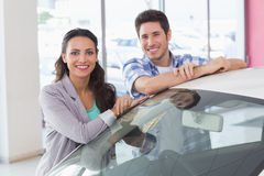 Smiling couple leaning on car Stock Images