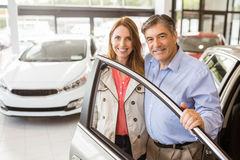 Smiling couple leaning on car Royalty Free Stock Images