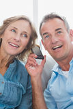 Smiling couple listening to mobile phone together Royalty Free Stock Photos