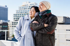 Smiling couple looking away. Against building Stock Photos