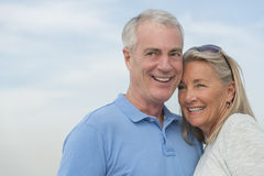 Smiling Couple Looking Away Against Sky. Senior couple smiling while looking away against sky Stock Image