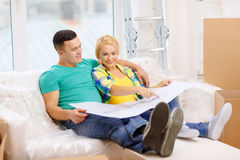 Smiling couple looking at bluepring in new home. Moving, home and couple concept - smiling couple relaxing on sofa and looking at blueprint in new home royalty free stock images
