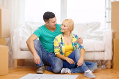 Smiling couple looking at bluepring in new home. Moving, home and couple concept - smiling couple relaxing on sofa and looking at blueprint in new home stock photos