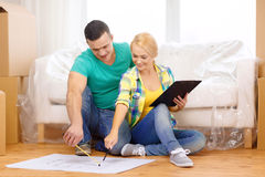 Smiling couple looking at bluepring in new home. Moving, home and couple concept - smiling couple relaxing on sofa and looking at blueprint in new home royalty free stock photography