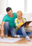 Smiling couple looking at bluepring in new home Stock Images
