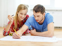 Smiling couple looking at blueprint at home. Repair, building, renovation and home concept - smiling couple looking at blueprint at home stock photo