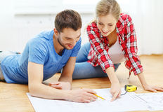 Smiling couple looking at blueprint at home Stock Image