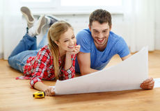 Smiling couple looking at blueprint at home. Repair, building, renovation and home concept - smiling couple looking at blueprint at home royalty free stock photography