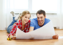 Smiling couple looking at blueprint at home. Repair, building, renovation and home concept - smiling couple looking at blueprint at home stock photography